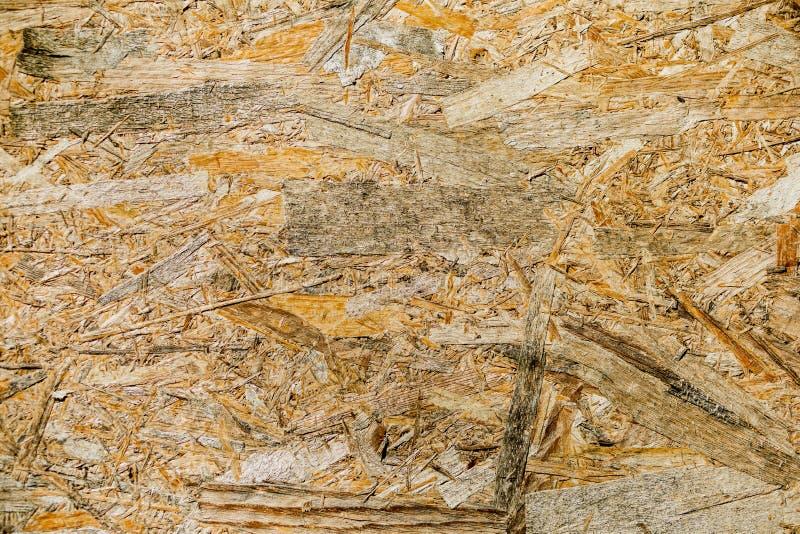 OSB-bräden göras av bruna sandpapprade trächiper in i en träbac royaltyfri foto
