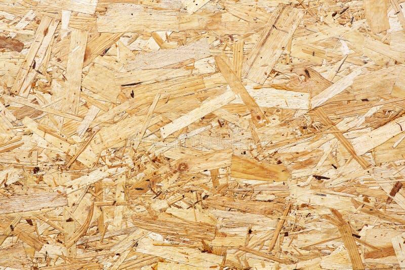 OSB-de raad wordt van bruine houten die spaanders gemaakt in houten achtergrond worden geschuurd Hoogste mening van houten het ve royalty-vrije stock foto