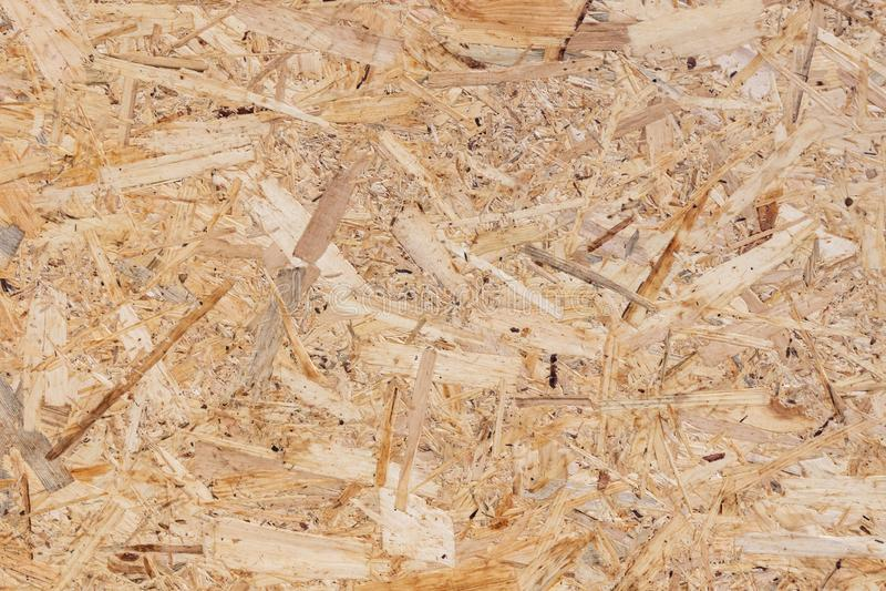 OSB-textuur van het materiaal - de gerecycleerde samengeperste houten spaanders plateren, triplextextuur, close-up stock afbeeldingen