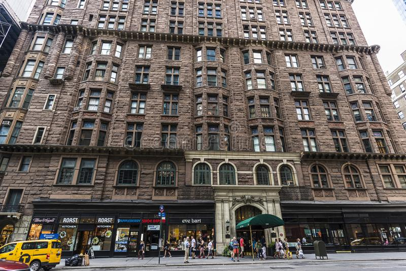 Osborne Apartments in Manhattan, New York City, USA. New York City, USA - July 28, 2018: Facade of Osborne Apartments with traffic and people around in Manhattan royalty free stock photography