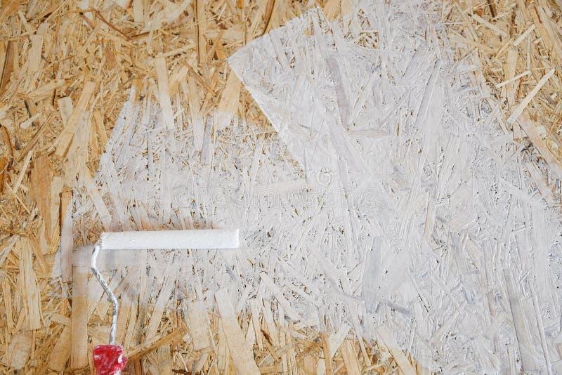 Osbplaat met witte verf met een rol wordt geschilderd die stock foto's