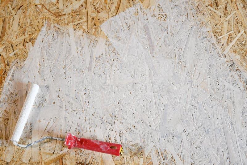 Osbplaat met witte verf met een rol wordt geschilderd die stock afbeelding