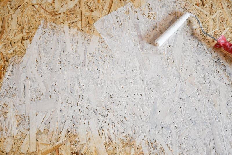 Osbplaat met witte verf met een rol wordt geschilderd die royalty-vrije stock fotografie