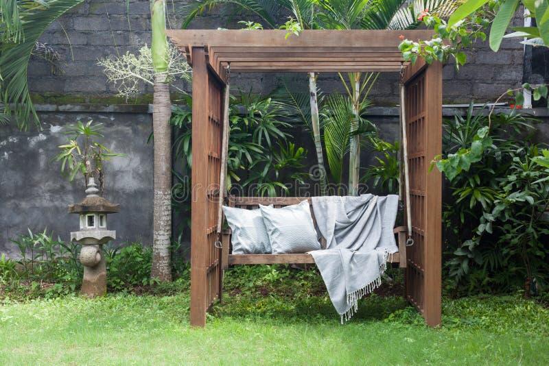 Oscilación de madera al aire libre clásico en el jardín verde con las almohadas y la manta fotografía de archivo libre de regalías