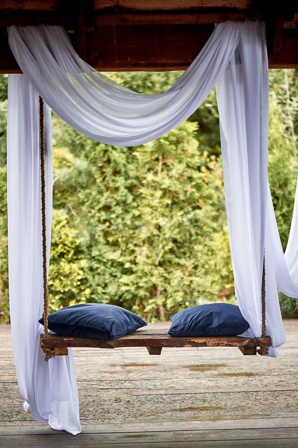 Oscilación de madera en el jardín, con los amortiguadores suaves azules Un lugar acogedor a relajarse foto de archivo libre de regalías