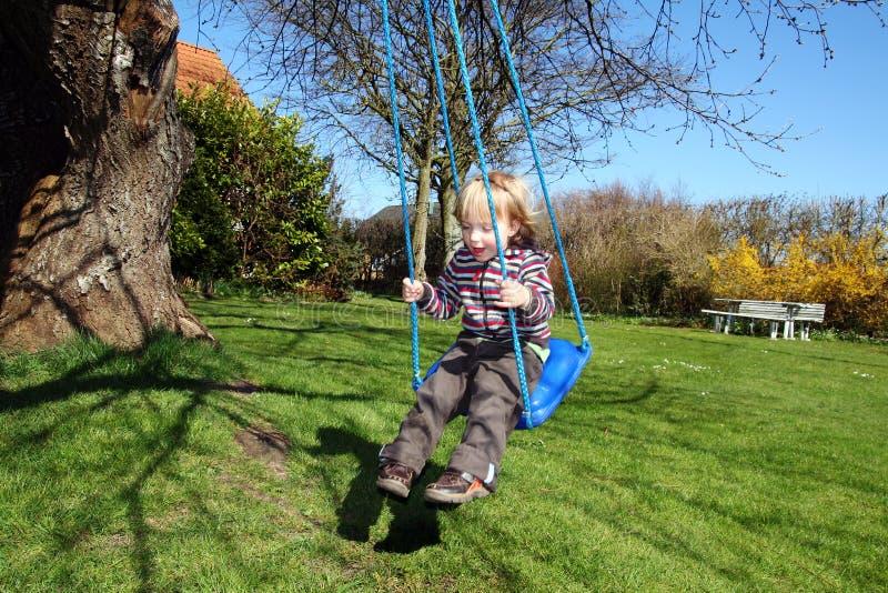 Oscilación del niño en jardín foto de archivo