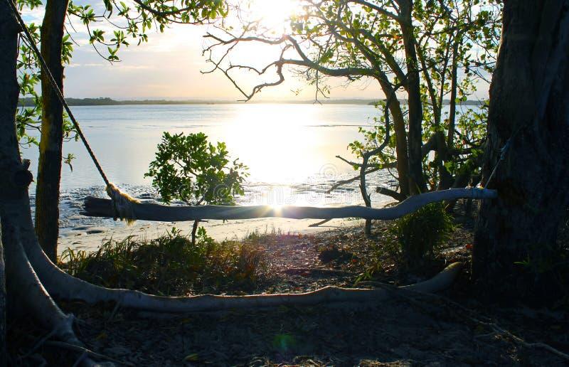 Oscilación hecho en casa para mirar la puesta del sol por el borde de las aguas con la llamarada de la lente foto de archivo libre de regalías