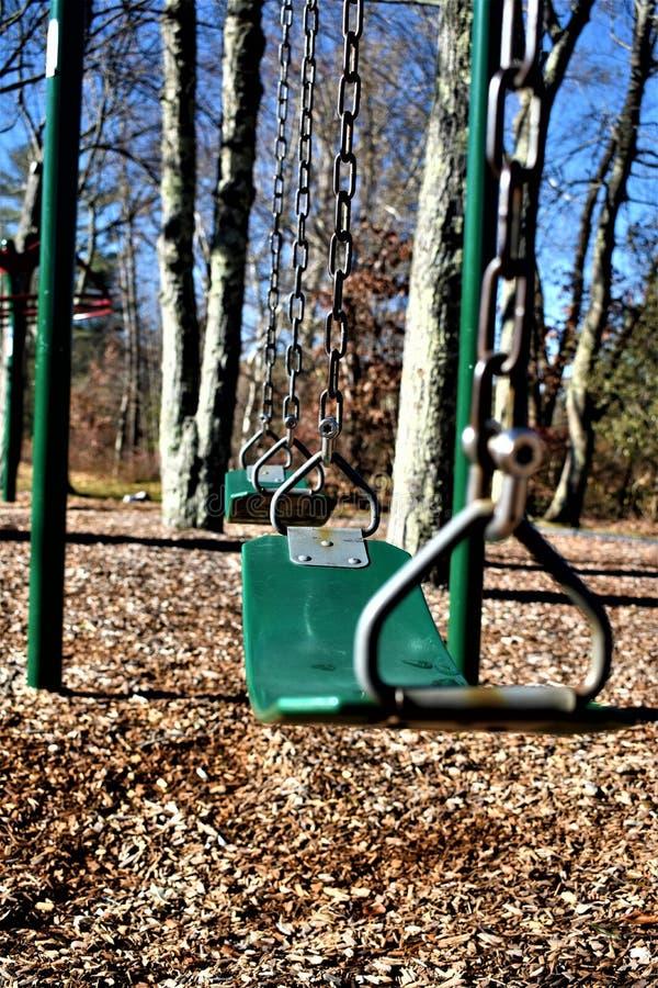 Oscilación verde en un parque del ` s de los niños imagenes de archivo