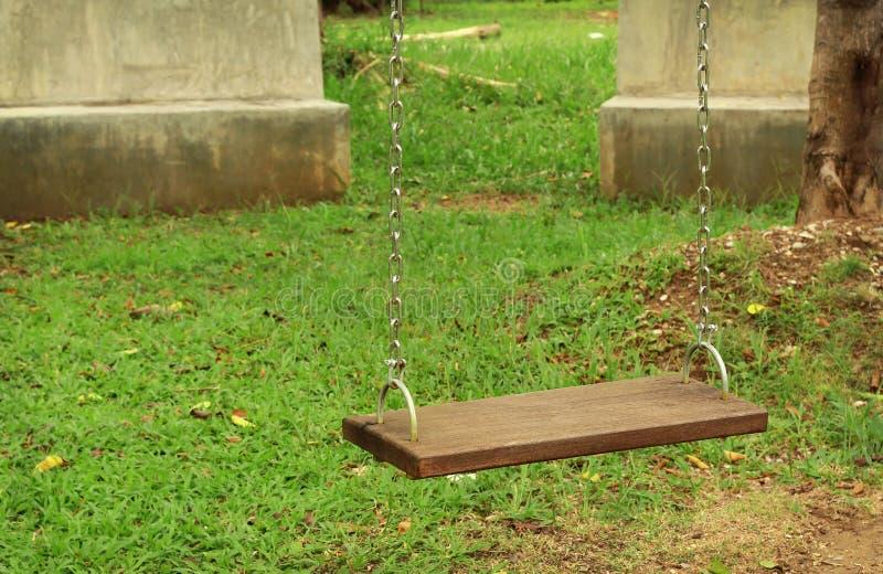 Oscilaciones de madera de cadena vacíos en yarda de las actividades en el parque público imágenes de archivo libres de regalías