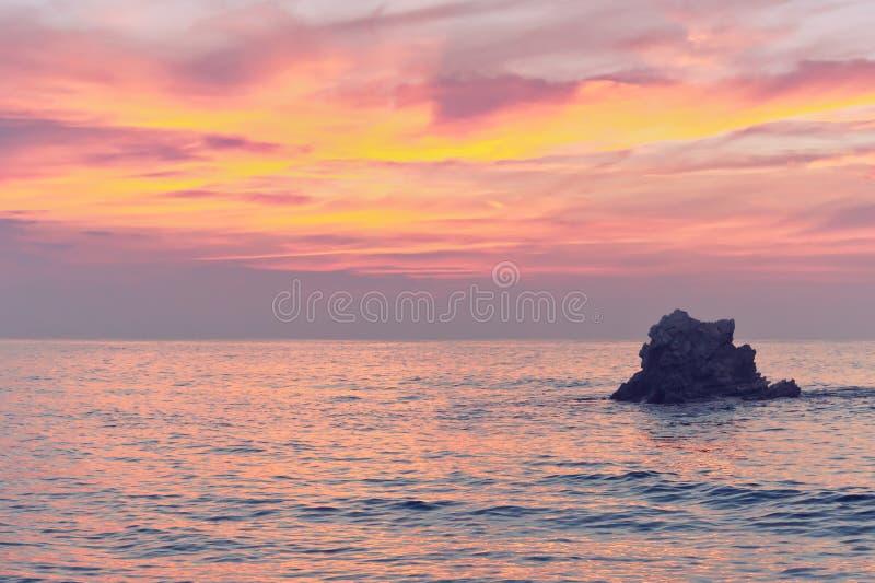 Oscile en la puesta del sol en el mar con colores rosados imagenes de archivo