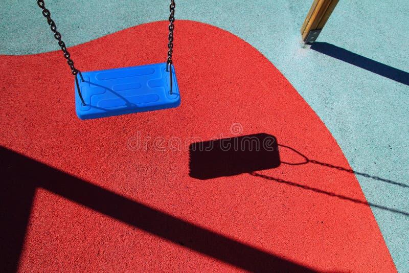Oscillation bleue de stationnement ou cour de jeu rouge d'enfants d'étage images stock