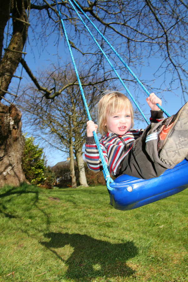 Oscillation d'enfant dans le jardin photos stock