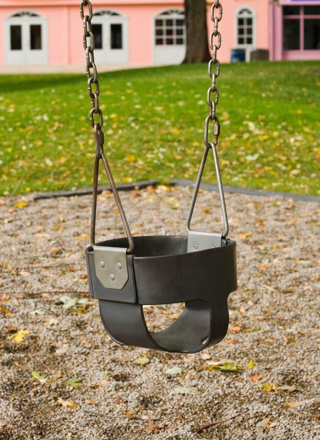 Oscillation d'enfant en bas âge de cour de jeu image libre de droits