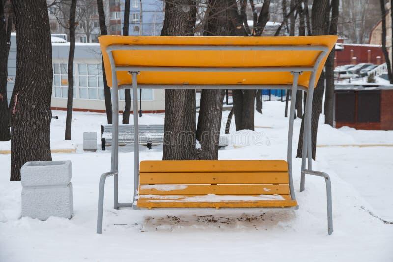 Oscillation de banc en parc d'hiver couvert de neige photo libre de droits