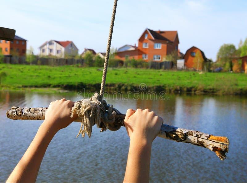 Oscillation de corde de prise de mains avant saut dans l'eau sur le lac et photographie stock libre de droits