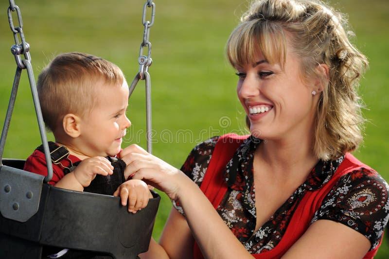 Oscillation, mère et enfant de cour de jeu photographie stock