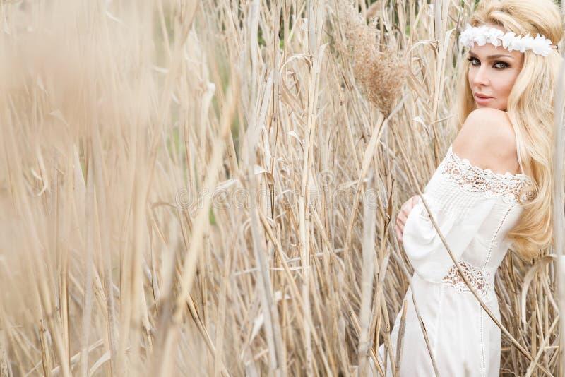 Oscillation naturelle sexy blonde renversante de femme sur une oscillation sur un arbre portant une robe de ressort photo libre de droits