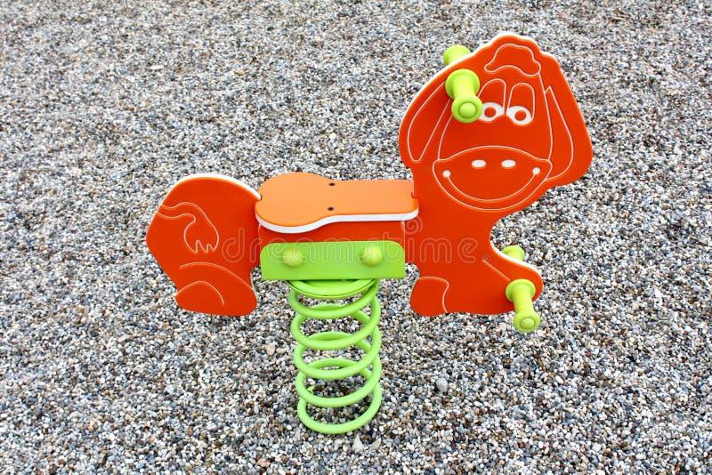 Oscillation orange de cavalier de ressort de poney d'équipement public extérieur de terrain de jeu images stock