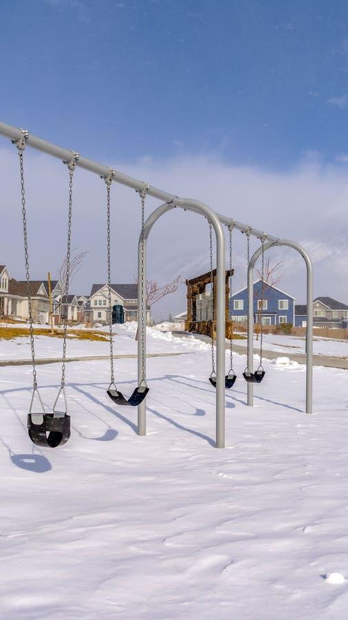 Oscillations verticales de bébé à un terrain de jeu couvert avec la neige propre un jour ensoleillé d'hiver photos libres de droits