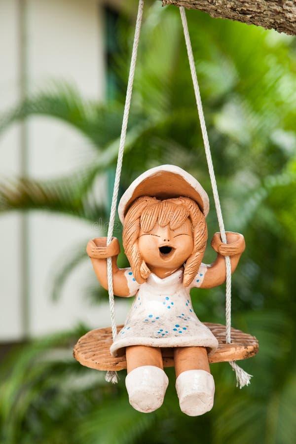 Oscillazione ceramica di seduta della bambola nel giardino fotografia stock