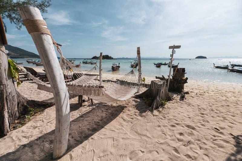 Oscillazione della culla della corda che appende sul legno sulla spiaggia con la barca di legno in mare tropicale immagine stock libera da diritti