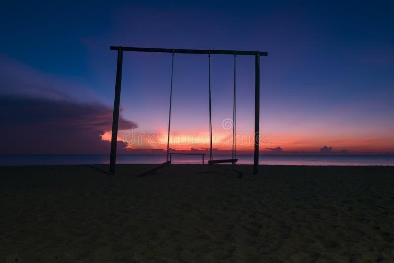 Oscillazione e bella spiaggia tropicale sopra alba crepuscolare magica immagini stock libere da diritti