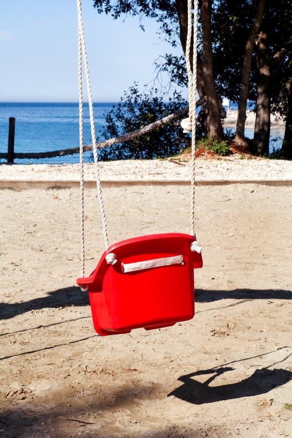 Oscillazione rossa sulla spiaggia fotografia stock
