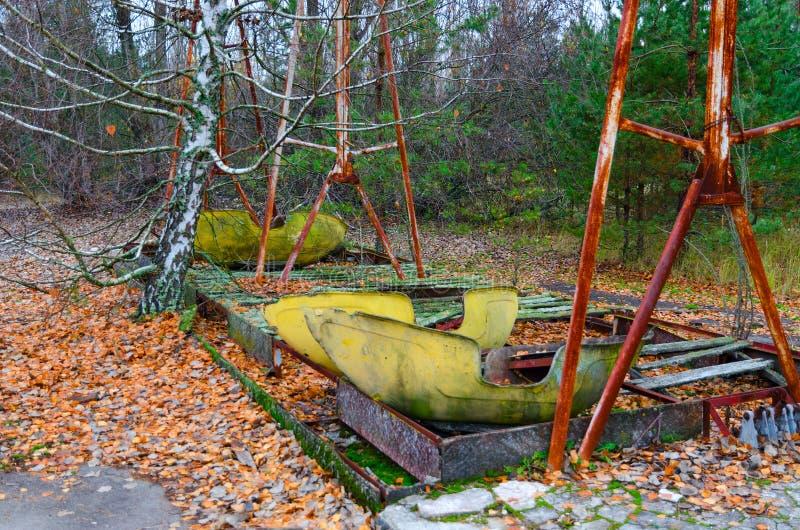 Oscillazioni al parco di divertimenti in città fantasma abbandonata di Pripyat, zona di alienazione di Cernobyl, Ucraina della ba fotografia stock