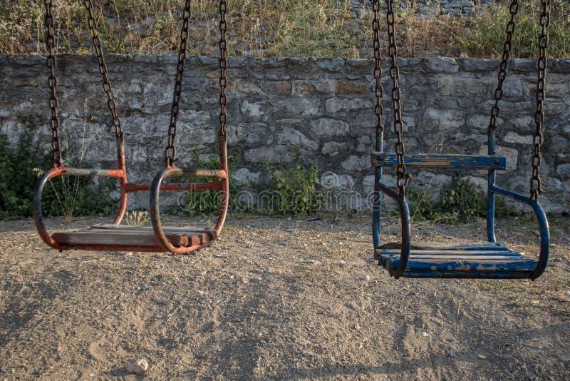 Oscillazioni dei bambini con una catena in un campo da giuoco fotografie stock libere da diritti