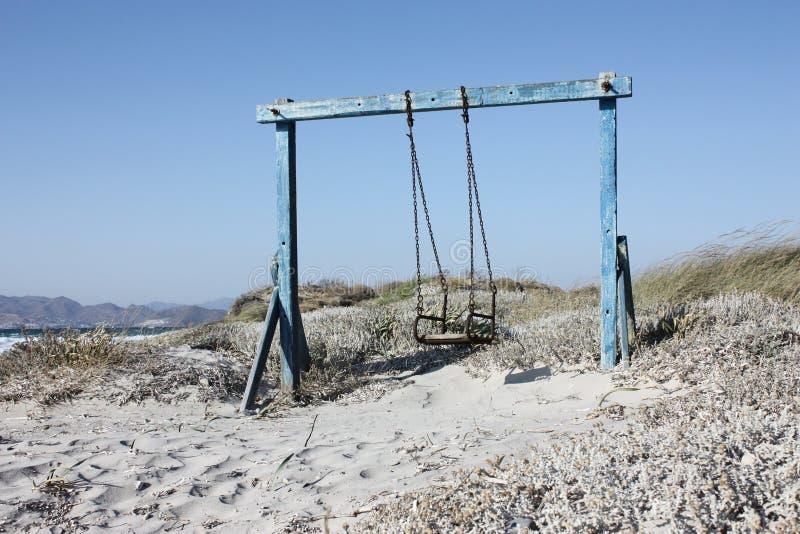 Oscilli alla spiaggia con la sabbia fotografia stock