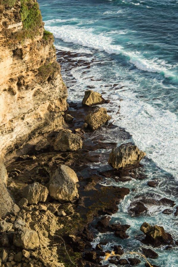 Oscilli ed ondeggi accanto alla scogliera alla spiaggia fotografia stock libera da diritti