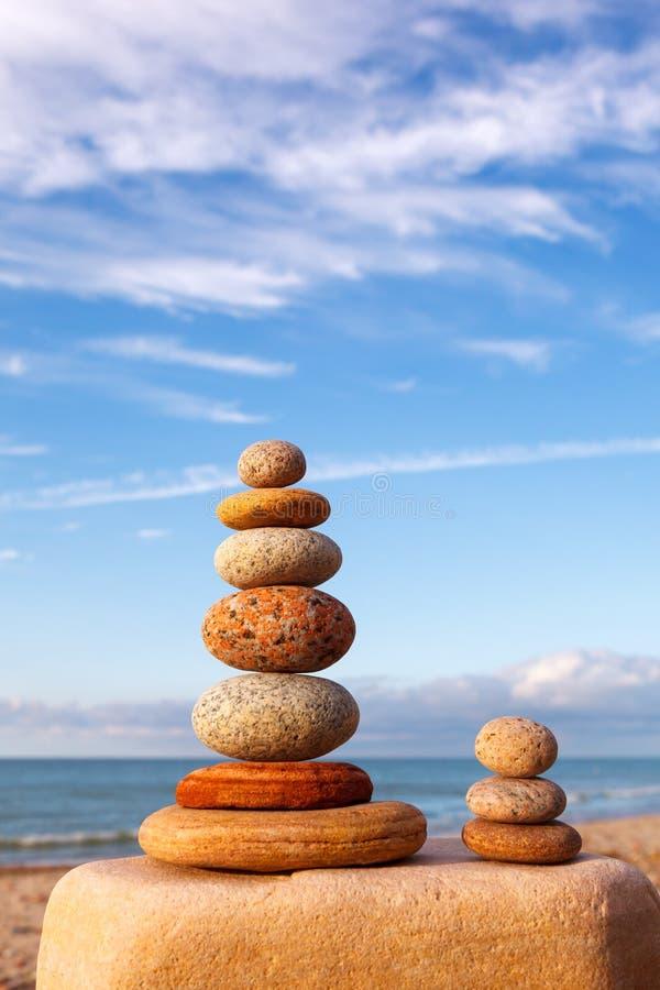 Oscilli la piramide di zen delle pietre bianche e rosa su un fondo di cielo blu e del mare fotografia stock libera da diritti