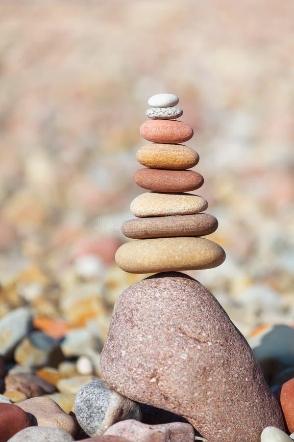 Oscilli la piramide di zen delle pietre bianche, rosse e gialle Concetto di equilibrio, di armonia e della meditazione fotografia stock libera da diritti