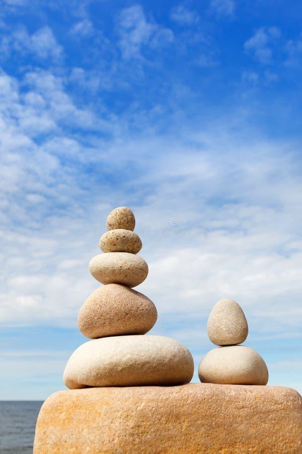 Oscilli la piramide di zen delle pietre bianche su un fondo di cielo blu e del mare immagine stock
