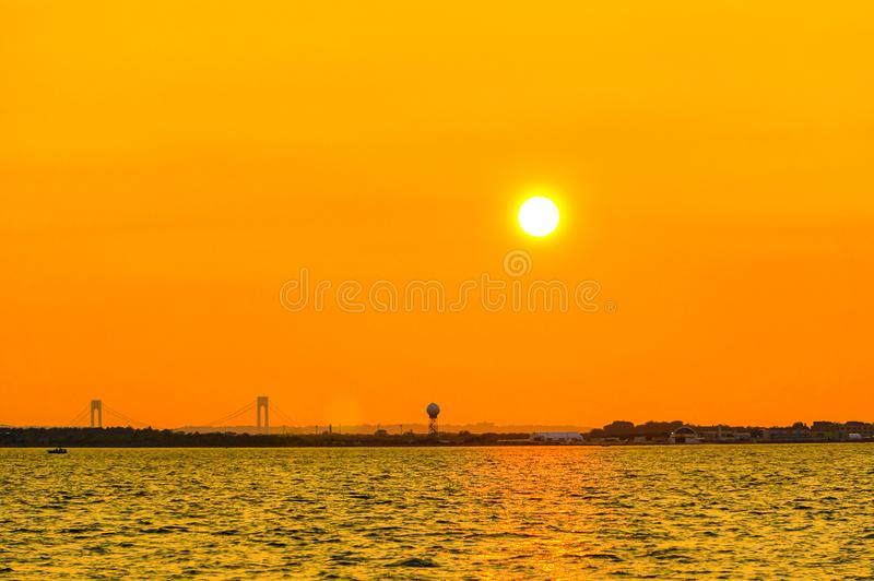 Oscuridad anaranjada en Nueva York con la opinión del puente de los Verrazzano-estrechos foto de archivo