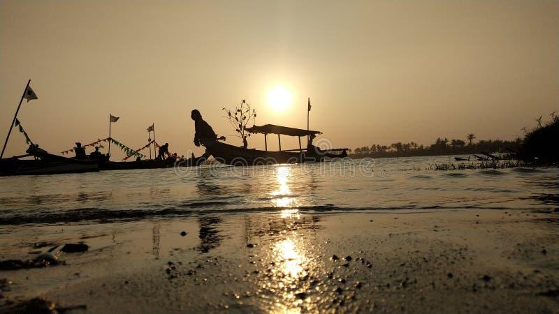 oscuridad cuando el sol fija al borde de una laguna romántica de la playa mientras que mira la sombra del barco foto de archivo libre de regalías