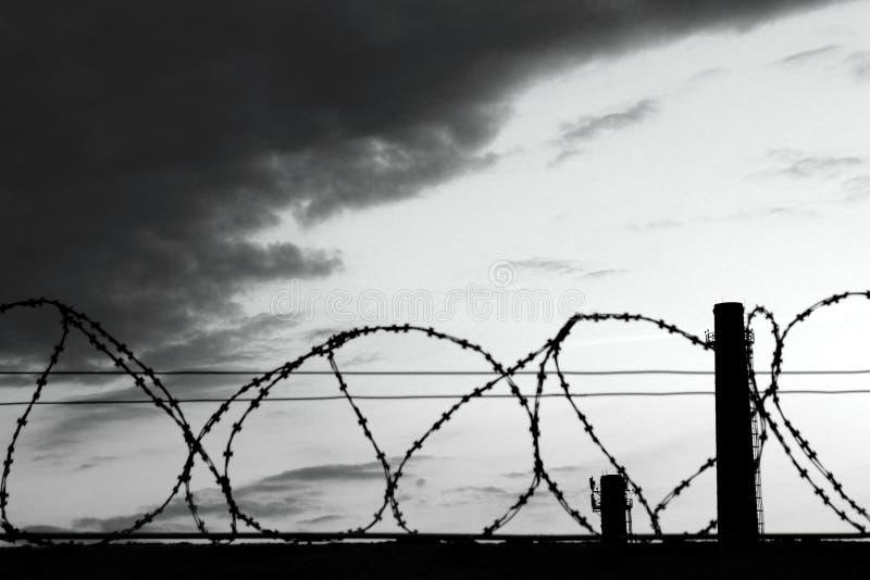 Oscuridad de la prisión de la cerca del alambre de púas foto de archivo