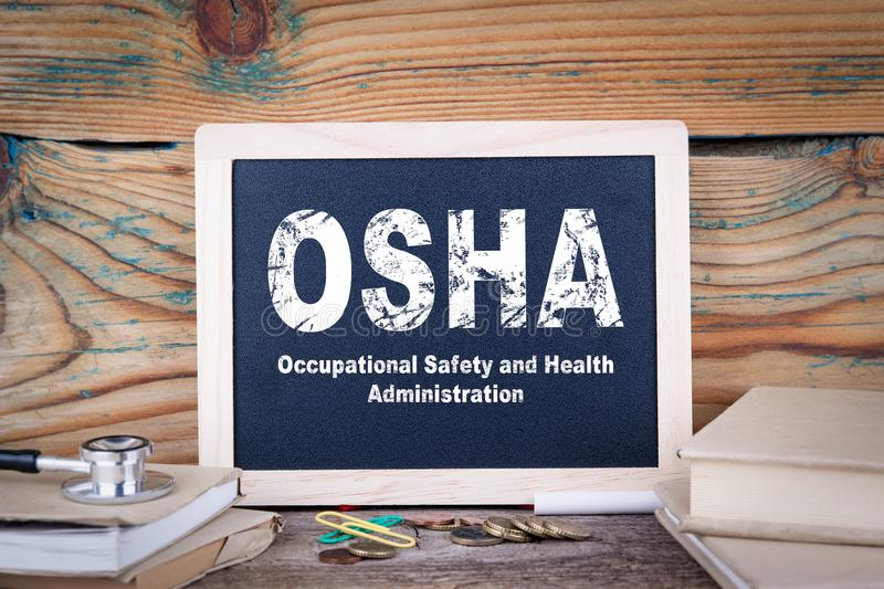 Osha, Occupational Safety and Health Administration. Chalkboard on a wooden background stock photography