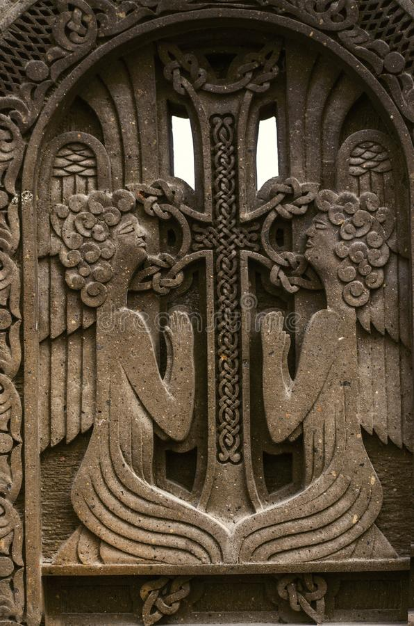 Two praying angels near the cross with intertwining ornament,engraved on dark volcanic stone. Oshakan,Armenia,19 Februar,2018:Two praying angels near the cross stock image