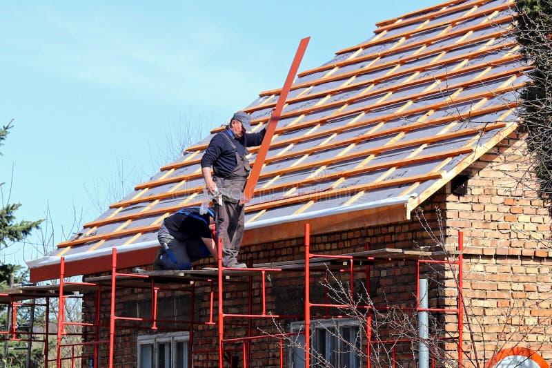 Osiek, Polen - april 18, 2018: Twee bouwers verbergen een dak op een baksteenhuis in het dorp Bouwwerkzaamheid op een kleine faci stock foto's