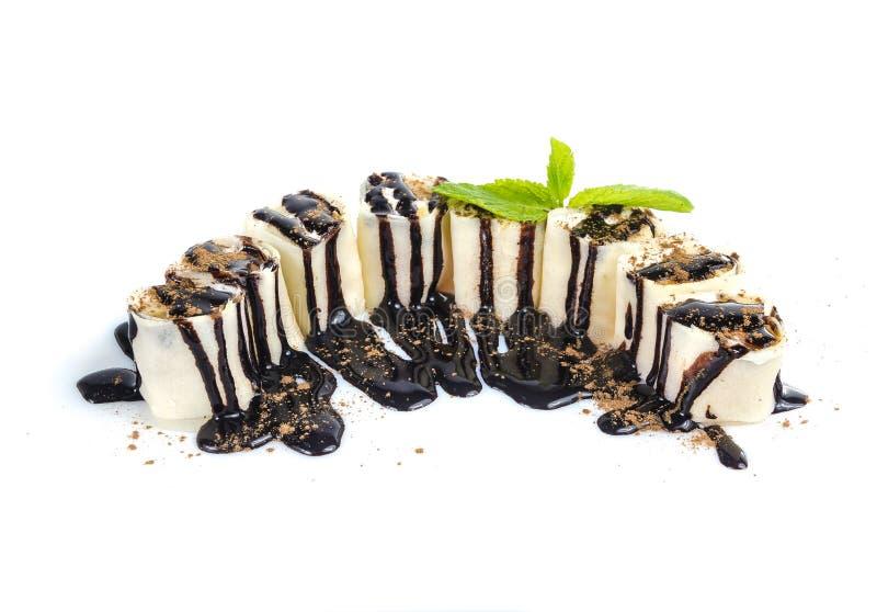 Osiem kawałków suszi jak torty z czekoladowym polewy i cacao proszkiem odizolowywającym na białym tle fotografia stock