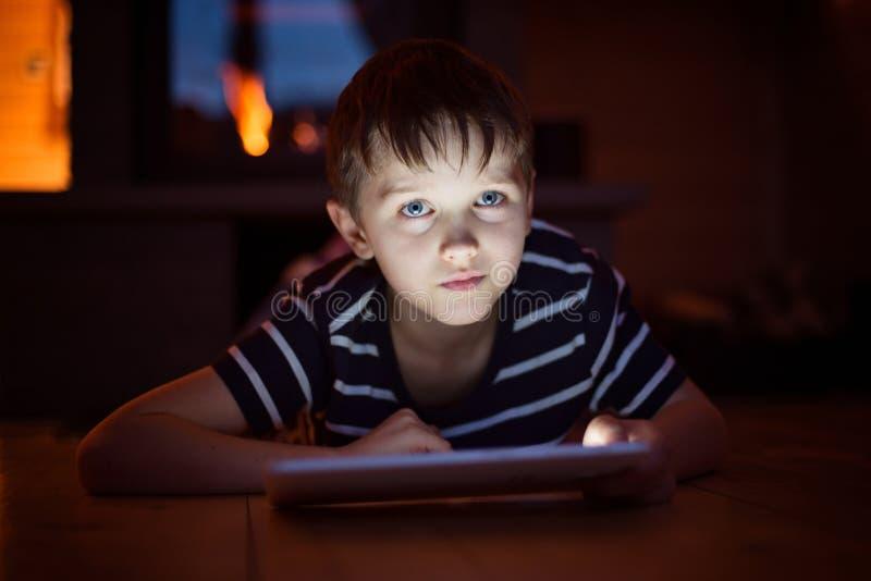 Osiem lat chłopiec używa cyfrową pastylkę zdjęcia royalty free