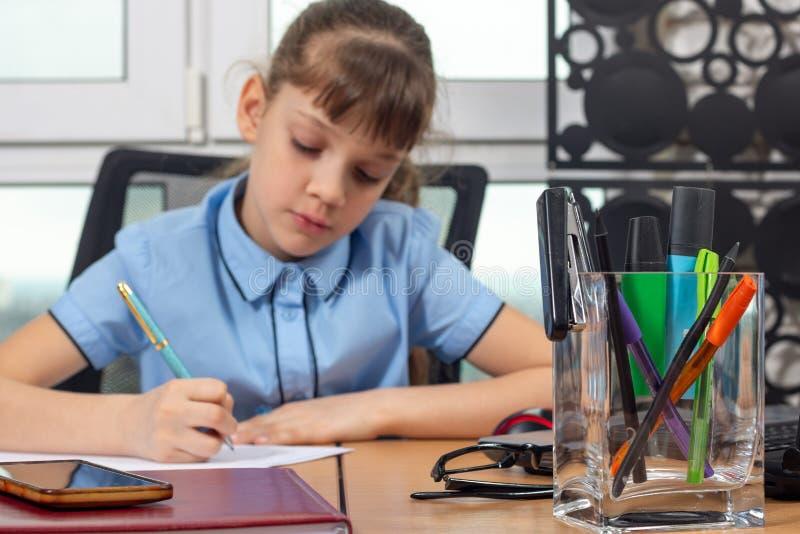Osiem lat dziewczyna pracuje w biurze, skupia się na biurowych dostawach obraz royalty free