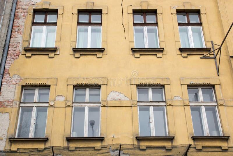 Osiem okno na fasadzie stary podławy koloru żółtego dom zdjęcie stock