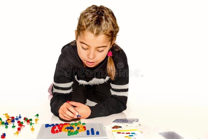 Osiem roczniaka dziewczyna bawić się z grze planszowa na bielu fotografia royalty free