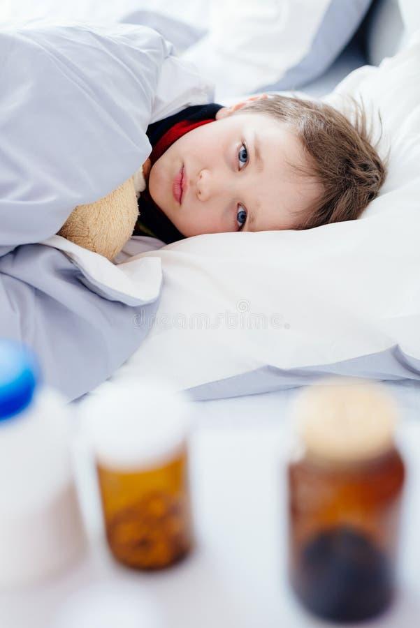 Osiem rok chorego chłopiec lying on the beach w łóżku obrazy stock