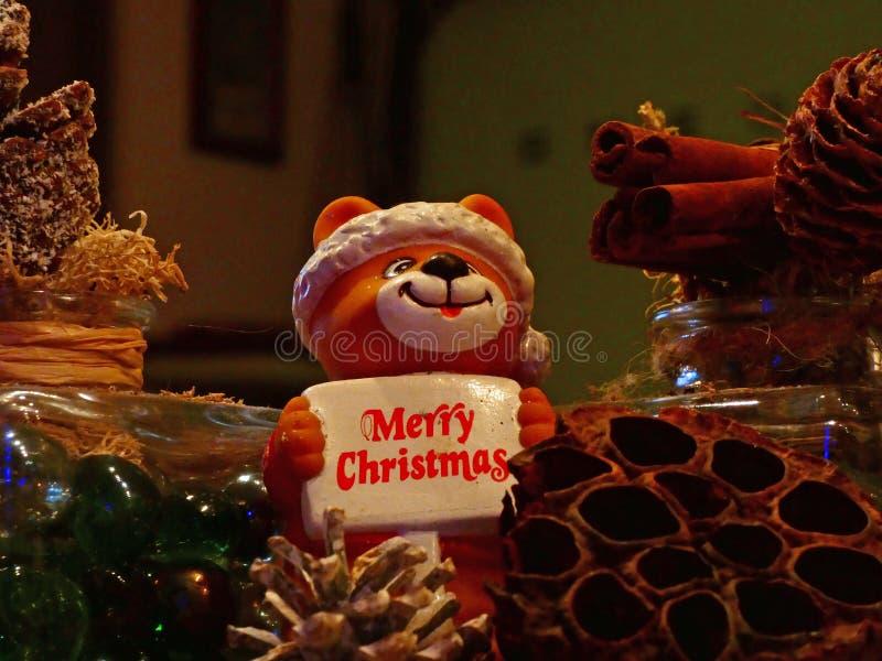 Osito vestido como santa claus sosteniendo un plato diciendo Feliz Navidad imagenes de archivo