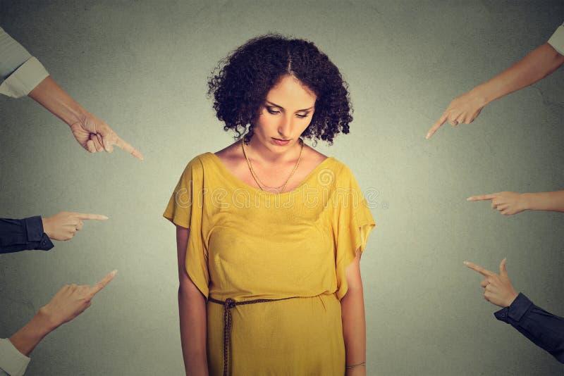 Oskarżenie osoby winna dziewczyna Smutna zaaferowana kobieta patrzeje w dół wiele palce wskazuje przy ona obrazy royalty free