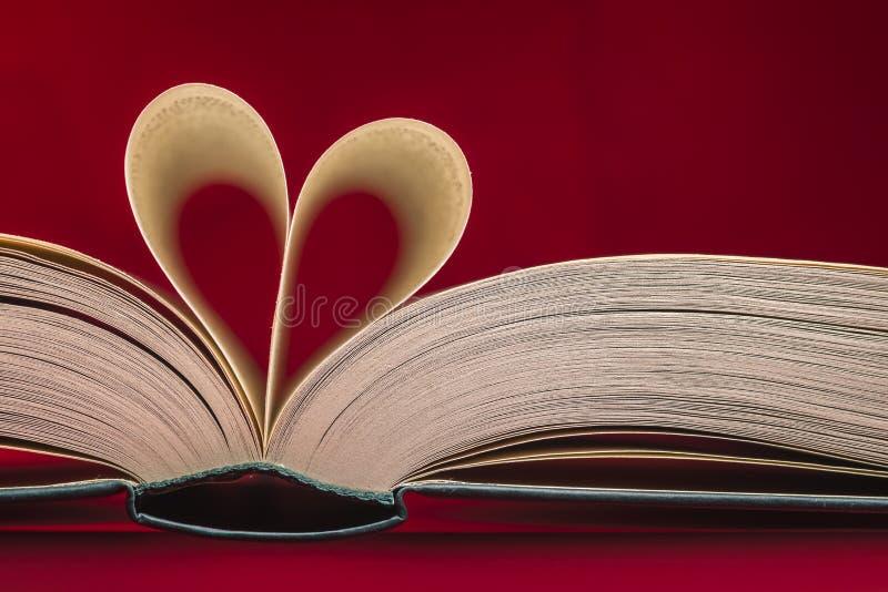 Oskarp hjärta som göras från boksidor över röd bakgrund royaltyfri foto