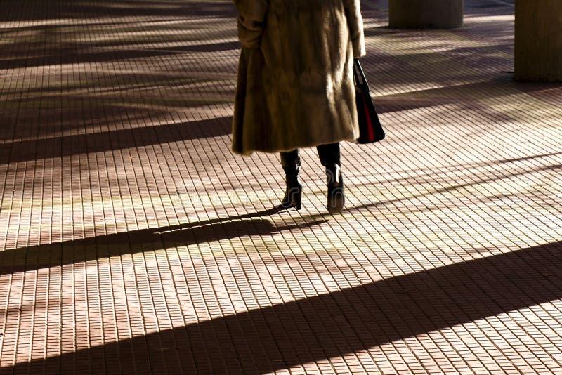 Oskarp konturskugga av ben av en kvinna i pälslag och kängor för höga häl som går på en stadsgallerigångbana arkivbilder
